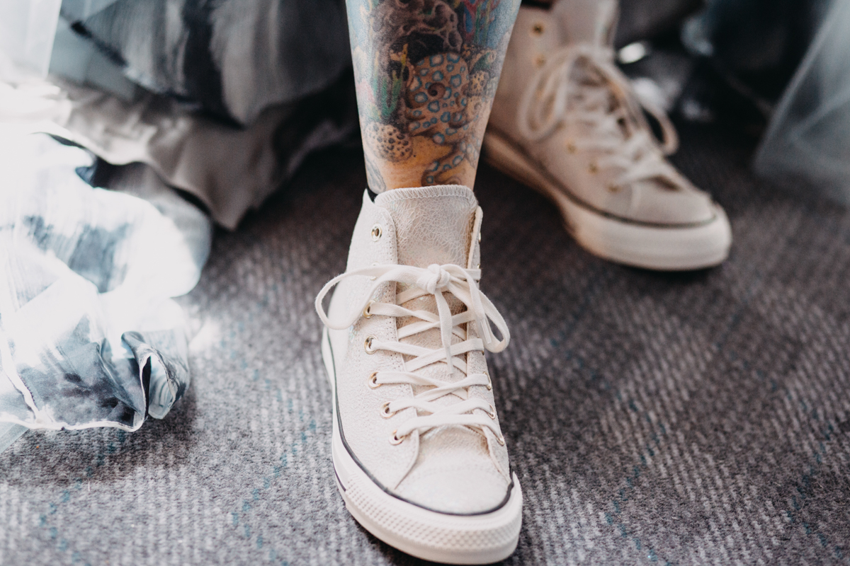 white leather wedding converse on tattooed bride